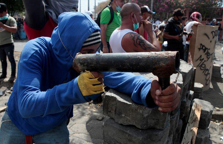 Een demonstrant vuurt met een zelfgemaakt wapen op de politie. Beeld REUTERS