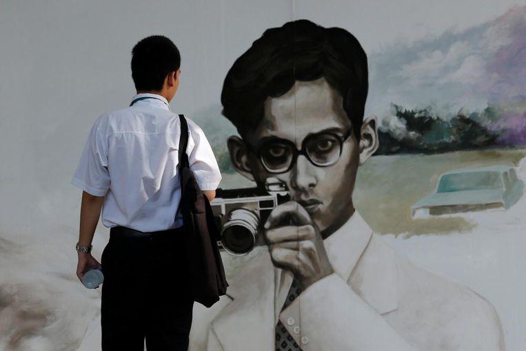 Een student kijkt naar een muurschildering van de Thaise koning in Bangkok. Beeld Reuters