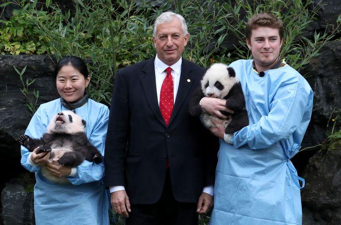 Eric Domb, CEO de Pairi Daiza, pose avec des soigneurs portant les bébés pandas