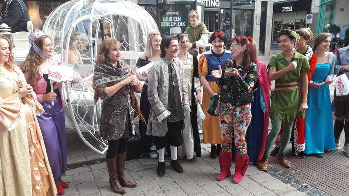 Organisator Karin Terwisse (derde van links) bekroont vrijwilliger Anouk Pauwels (derde van rechts) met het Gouden Sprookjesei van het Sprookjesfestival.