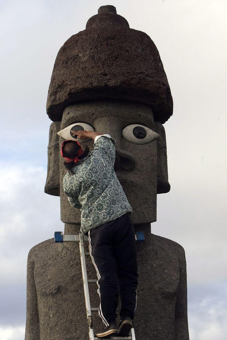 Een eilandbewoner werkt aan de restauratie van één van de bekende beelden op het eiland. Beeld EPA