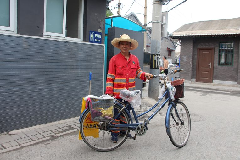 Een schoonmaker voor het oude toilet in Liangjiayuanxi-hutong. Beeld Leen Vervaeke