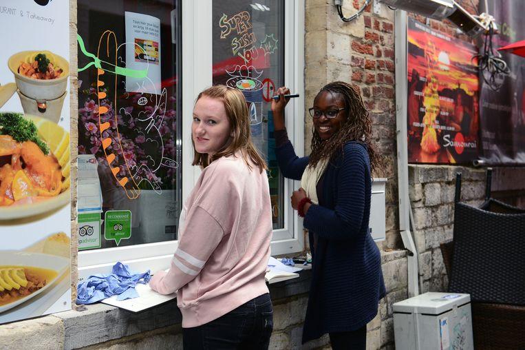 Enkele leerlingen van De Wijnpers versieren een vitrine in de Muntstraat met hun tekeningen.