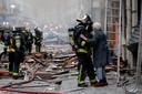 Een oudere dame wordt door een brandweerman in veiligheid gebracht.
