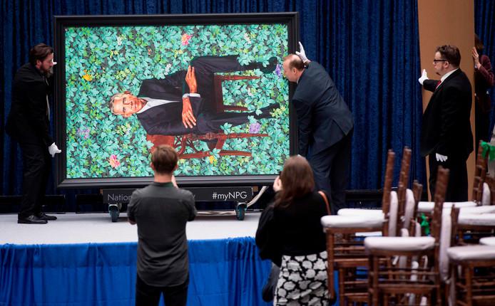 Medewerkers tillen het portret dat de Amerikaanse kunstenaar Kehinde Wiley maakte van Barack Obama naar zijn definitieve plek in het Smithsonian's National Portrait Museum in Washington. Foto Saul Loeb