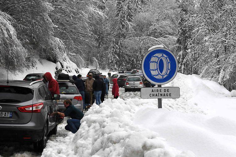 Gestrande toeristen monteren sneeuwkettingen op hun auto.