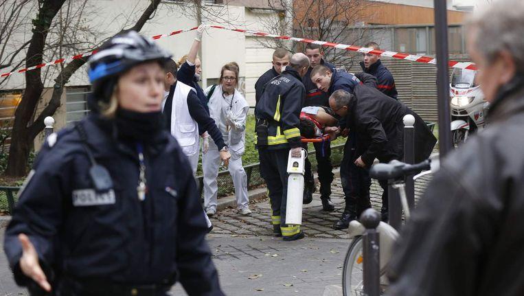 Franse politie draagt een gewonde op een stretcher weg van de redactie van Charlie Hebdo. Beeld reuters