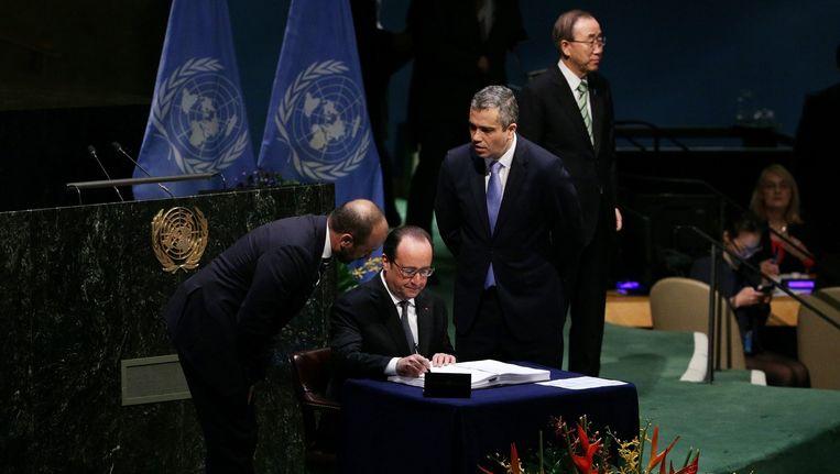 De Franse president Francois Hollande ondertekent het akkoord. Rechts de secretaris-generaal van de Verenigde Naties Ban Ki-moon. Beeld epa