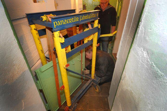 Inhangen van deuren in bunker Park Toorenvliedt - voor Lex Weijermans - achter staand Kees van Klinken en verscholen links Henk Adriaanse