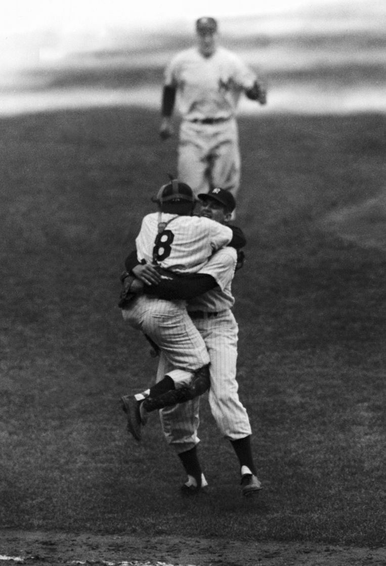Yogi Berra springt in de armen van pichter Don Larsen, na Larsens perfect game in oktober 1956. Beeld ap