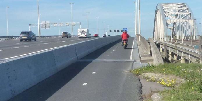 Het fietspad over de Jan Blankenbrug over de Lek in Vianen is smal en ligt vlak langs het voorbijrazende snelwegverkeer. Rechts de oude boogbrug.