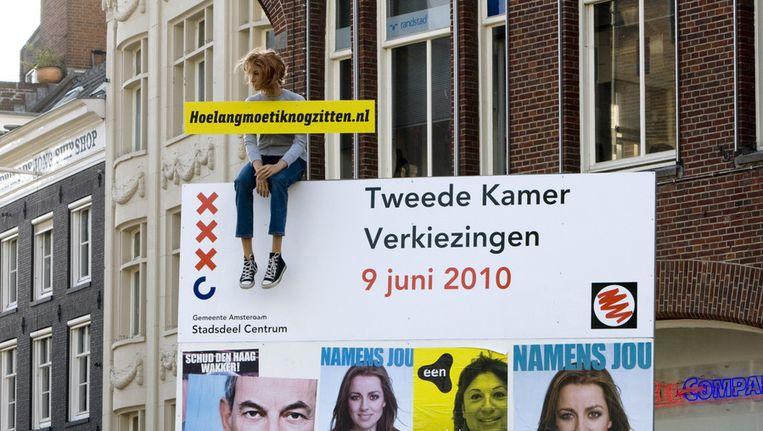 De FNV voerde in 2010 actie tegen de jeugdwerkloosheid, met deze pop op een verkiezingsbord aan het Amsterdamse Muntplein. Om de nek hangt een bord met de tekst 'Hoe lang moet ik nog zitten.nl.' Beeld ANP