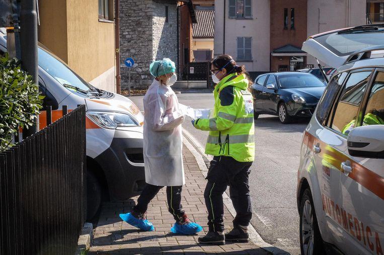 Gezondheidsmedewerkers komen iemand ophalen die vermoedelijk besmet raakte met het nieuwe coronavirus in Nembro, nabij Bergamo.