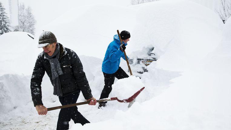 Veel voertuigen van de toerrijders die naar huis willen zijn bedolven onder een dik pak sneeuw. Beeld ANP