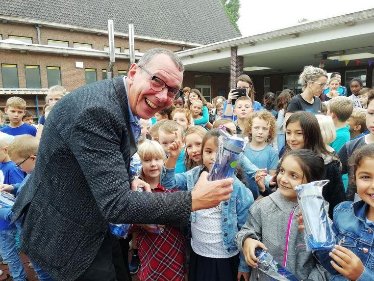 Herman Verbruggen deelt drinkbussen uit.