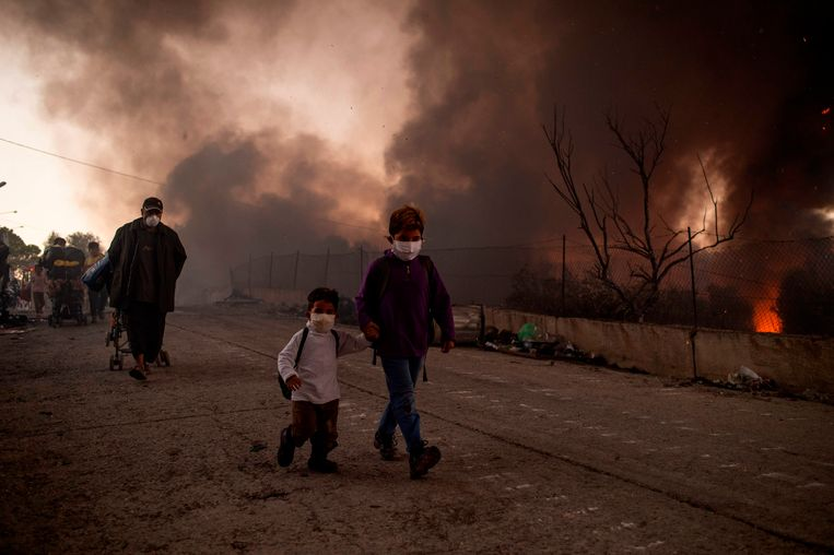 Duizenden mensen brachten de eerste nacht na de branden die woensdag het grootste deel van het kamp in as legden, door in de open lucht op de straten rond het kamp. Beeld AFP