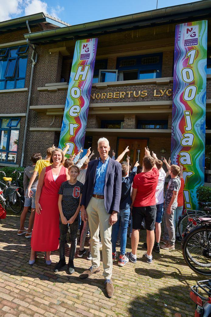 De banieren hangen aan het Norbertuscollege. Vooraan vlnr collegedirecteur Vivian van der Wielen-Bik, de jongste brugklasleerling Staf Damen en de oudste docent Rob de Mooij.
