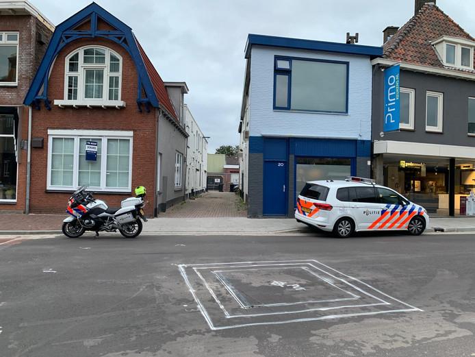 De politie doet onderzoek achter een woning