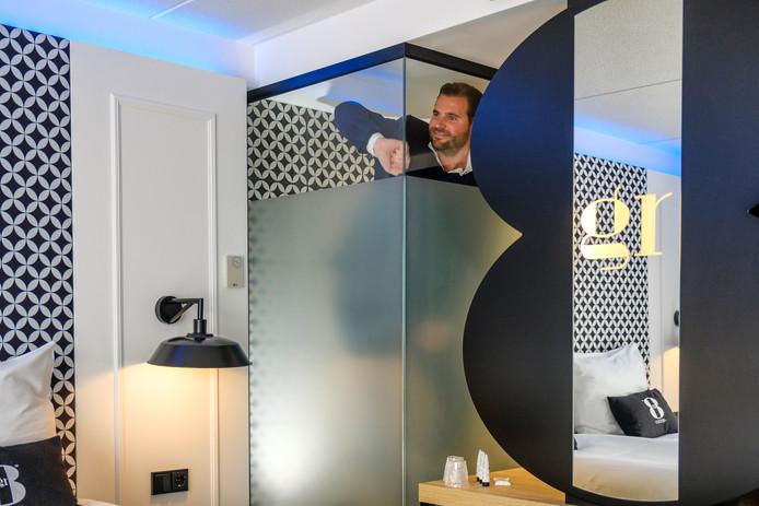 Martien Heinrichs, een van de drie eigenaren van GR8, poetst het badkamerraam in een van de kamers nog even op.
