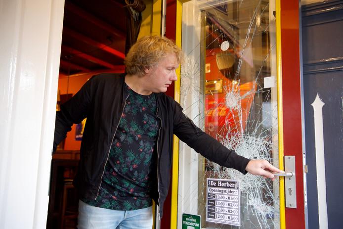 Kroegeigenaar Hans van Lingen bij de zwaar beschadigde toegangsdeur van De Herberg, een beeld uit november vorig jaar.