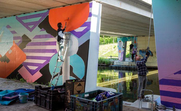 Een tunnel bij de Anthony Fokkerweg bij het Beatrixkanaal. Kunstenaars Johan Moorman en Vincent Huibers (r) zijn de tunnels aan het beschilderen.