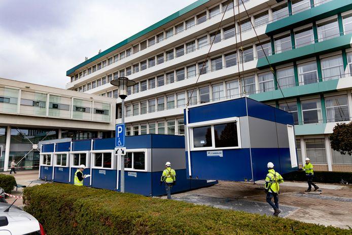 Medewerkers van De Meeuw plaatsen dinsdagmorgen de noodgebouwen voor het St. Jans Gasthuis.