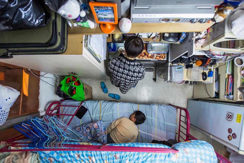 Een vrouw en haar zoon in hun appartement van 5,5 m2 in Hongkong, waarvoor ze maandelijks omgerekend 438 euro betaald. Beeld Reuters