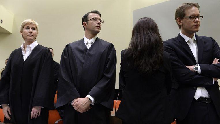 De advocaten van een van de verdachten, die haar rug naar de fotografen heeft toegekeerd. Beeld afp
