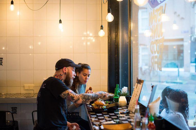 Vegan Junk Food Bar is een echte snackbar, witbetegeld, met wat hoge tafels en een aanschuifbarretje langs de muur Beeld  Mats van Soolingen