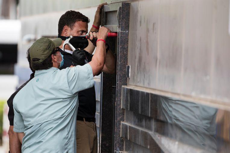 Federale agenten en een slotenmaker proberen de deur te openen. Beeld AP