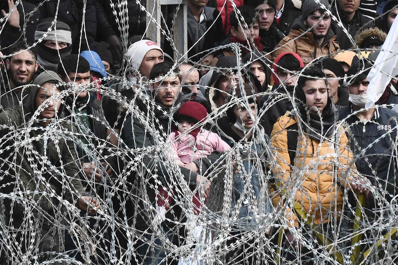 Een man met kind te midden van de wachtende vluchtelingen achter scheermesdraad op de grens tussen Turkije en Griekenland.