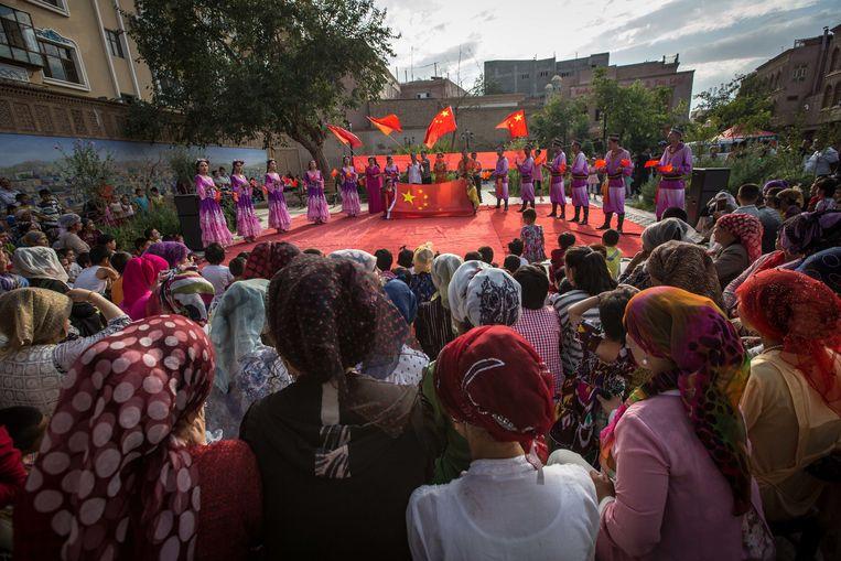 Oeigoeren kijken naar een traditionele dans in Kashgar, Xinjiang. Beeld LightRocket via Getty Images