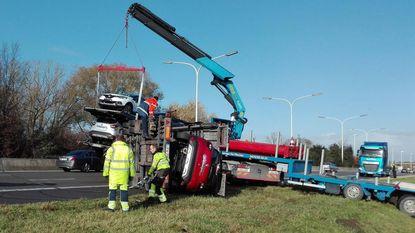 Vrachtwagen met gloednieuwe auto's kantelt
