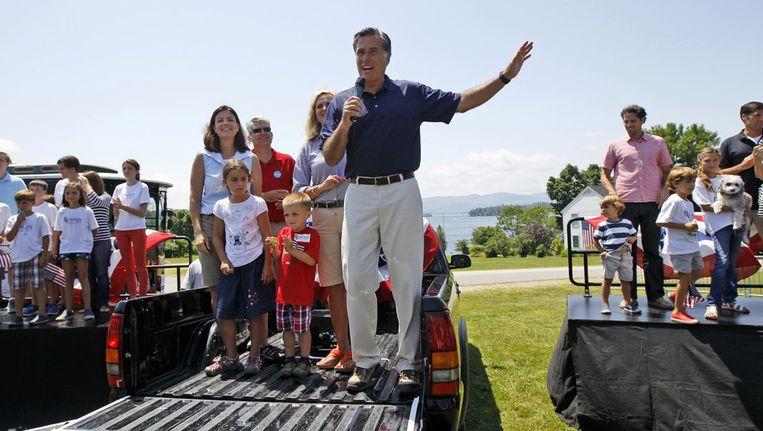 Mitt Romney spreekt mensen toe vanaf een pick-up. Naast hem zijn vrouw Ann. Beeld ap