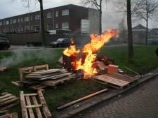 Brandende vuurtonnen en autobanden op grasveld in Tiel