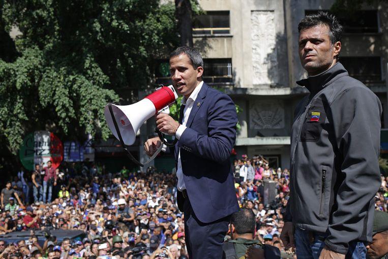 Guaidó spreekt zijn aanhangers toe, naast hem Leopolso López. Beeld AFP