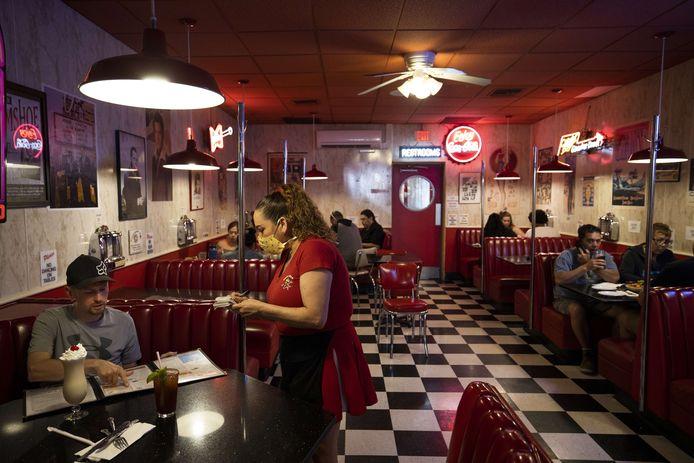 Een restaurant in de VS waar de serveerster een mondkapje op heeft.