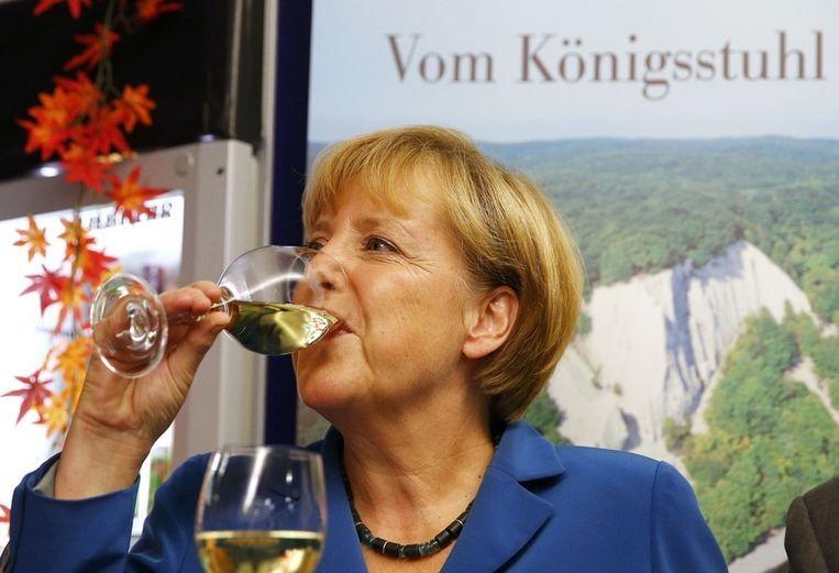 Angela Merkel drinkt een glas wijn nadat zondagavond de eerst uitslagen van exitpolls zijn binnengekomen. Beeld reuters