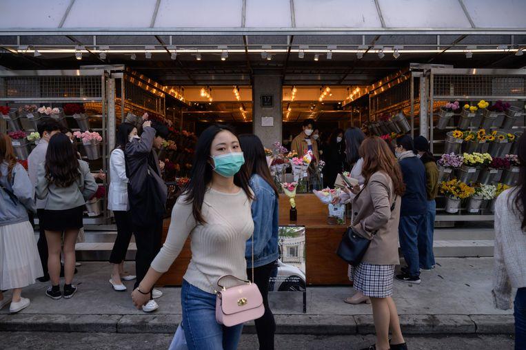 Mensen dragen een gezichtsmasker op straat in Yeonnam, Seoul.  Beeld AFP