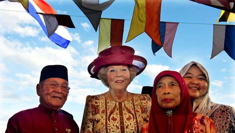 Koningin Beatrix wordt verwelkomd door Pengarah Haji Mokti bin Mohammed Salleh (L), het dorpshoofd van het traditionele waterdorp Tamoi Tengah, en zijn familie. Beeld anp
