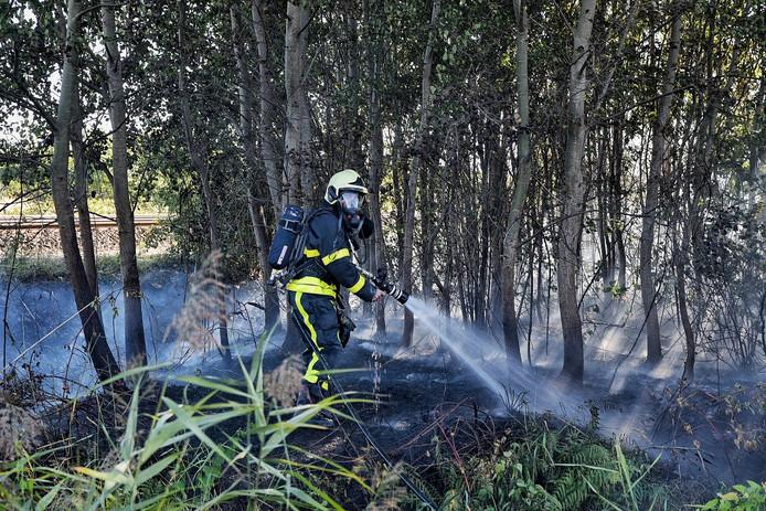 Bermbrand waarbij brandweerauto omvalt