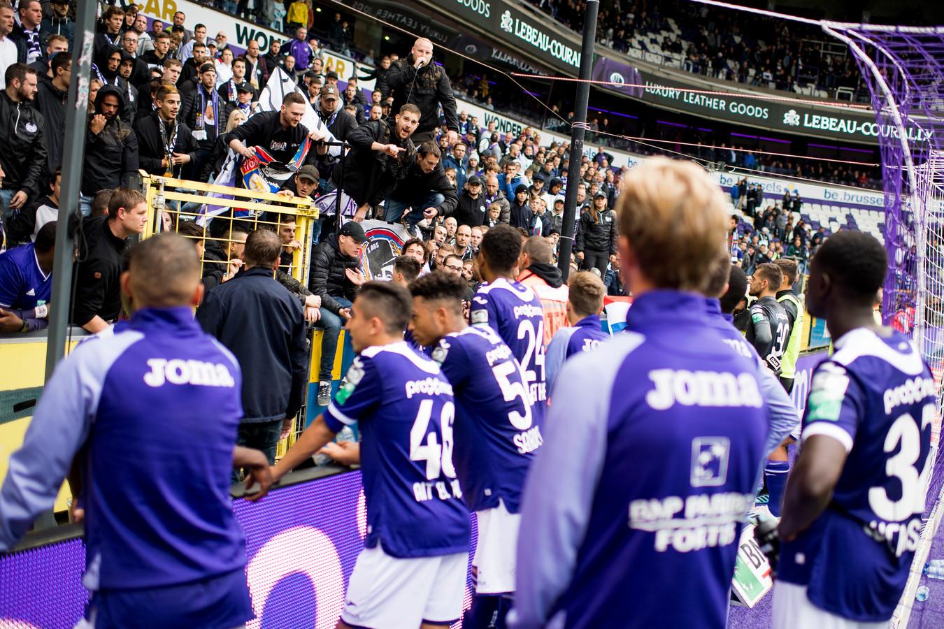 De spelers van Anderlecht proberen de boze supporters tot bedaren te brengen.
