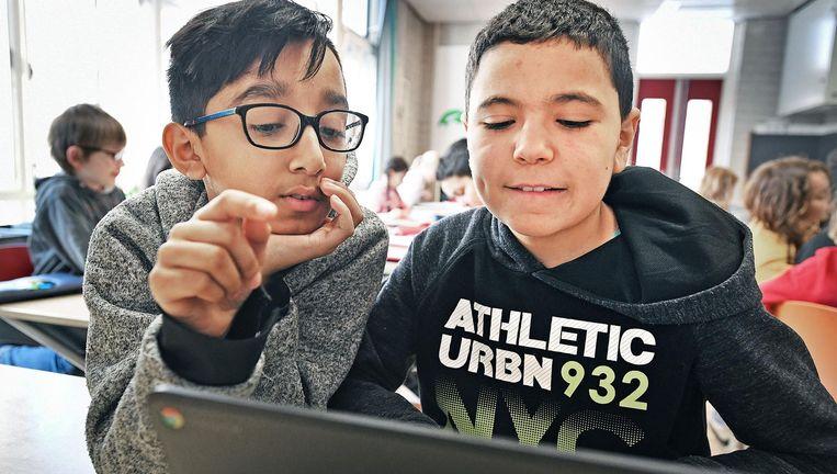Kinderen op de 'Coen' in Amsterdam-Oost werken na schooltijd nog even verder achter de laptop. Beeld Guus Dubbelman / de Volkskrant