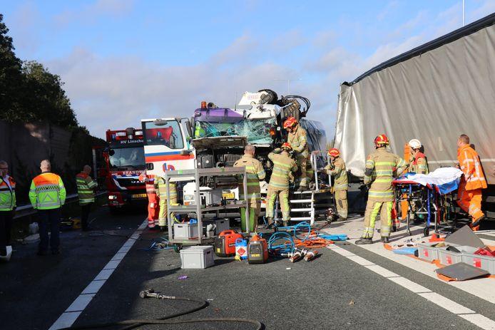 Bij een ongeval op de A12 is een vrachtwagenchauffeur bekneld geraakt in de cabine. De brandweer probeert de chauffeur te bevrijden.