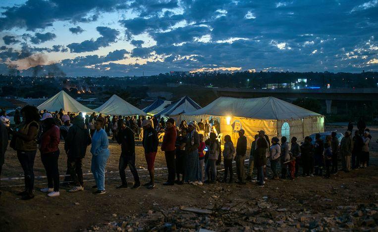 Inwoners van township Alexandra in Johannesburg staan in de rij voor een stemlokaal. Beeld AP