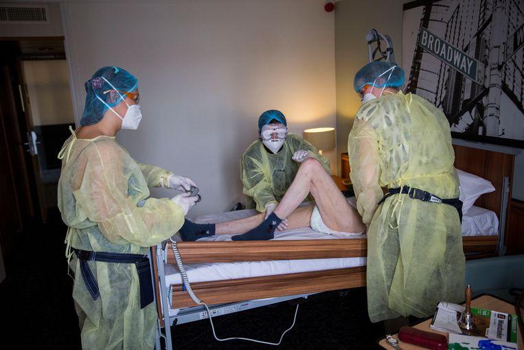2 april, in een coronacentrum in Roermond. Drie verpleegkundigen zijn in de weer met een oudere man die aan COVID19 lijdt.  Beeld Arie Kievit