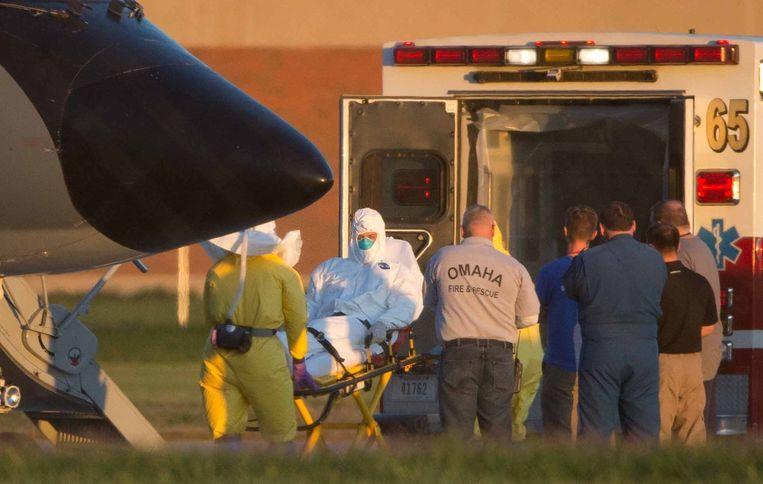 Ashoka Mukpo wordt op een brancard van het vliegtuig naar een gereedstaande ambulance gereden die hem naar het ziekenhuis vervoert. Beeld null