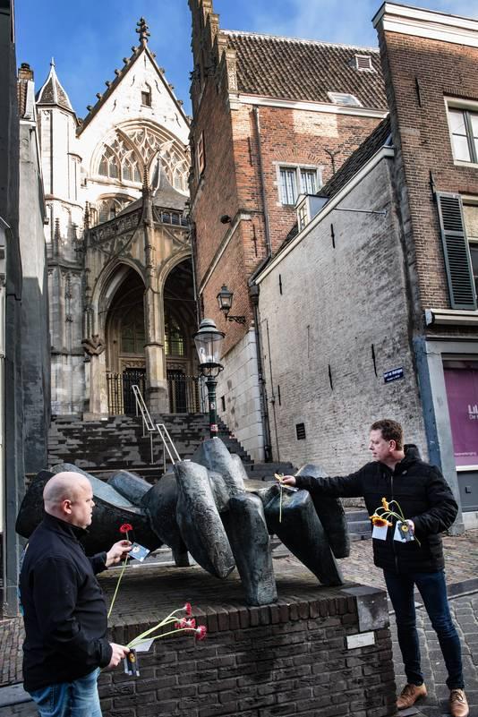Johan Tiesnitsch (links) en Jacco Danen leggen bloemen bij het standbeeld van Mariken in het centrum van Nijmegen.