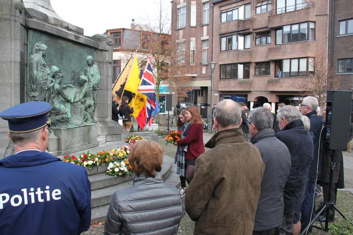 Wethouder Van Merwerode (rechts) tussen de mensen die vrijdag bloemen legden bij het monument.