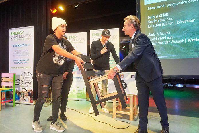 Wethouder Johan van der Schoot ontvangt de 'Stoel van de Toekomst' van Jade en Rahmo, leerlingen van het Mondriaan College in Oss.
